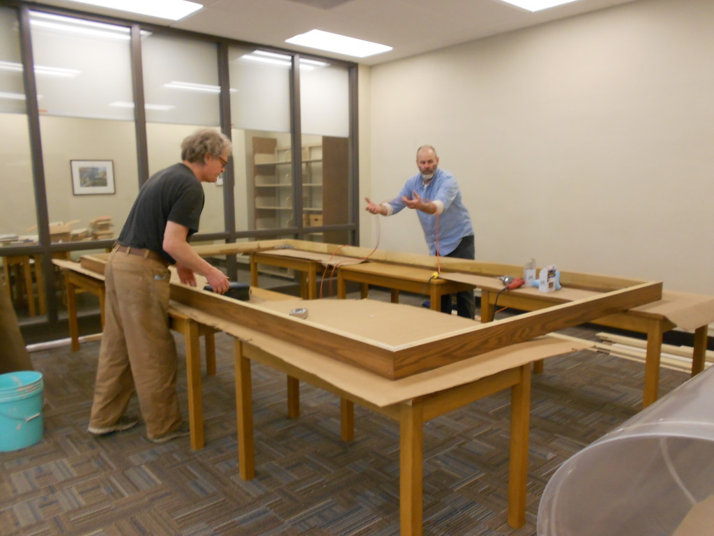 The oak frame after assembly with framer Bill Renschler, left, and his assistant Mark.   The frame was brought up the library disassembled and assembled onsite.  The frame pieces were carried up a stairwell where the stairwell windows had to be opened and the frame pieces slipped out the window to clear the stairwells' hairpin turns.