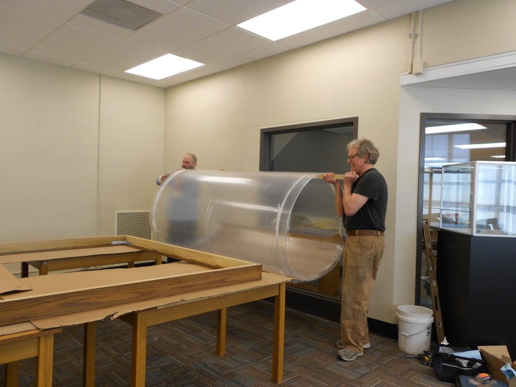 The unrolling of the Plexiglas, the map's new protective glazing.