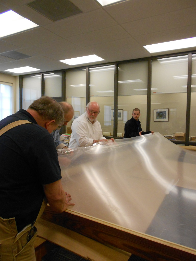 All hands on deck to roll out the Plexiglas.  Kevin Grace, center, Head of the Archives and Rare Books Library.