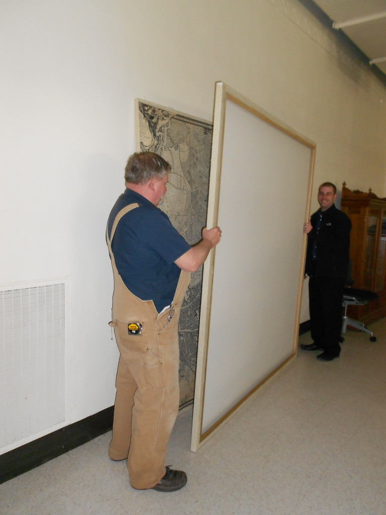The map sections back together and being admired by our carpenter, Alan, and library facilities coordinator, Joe Volker.