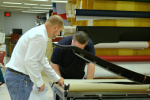 Chris showing Cade Stevens from the Classics Library how to use the board shears to cut his cloth.