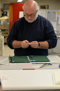 Kevin Grace, head of the Archives and Rare Books Library (UC), adhering all his Velcro pieces.